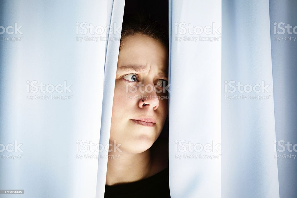 Worried and suspicious young woman peers through closed drapes royalty-free stock photo