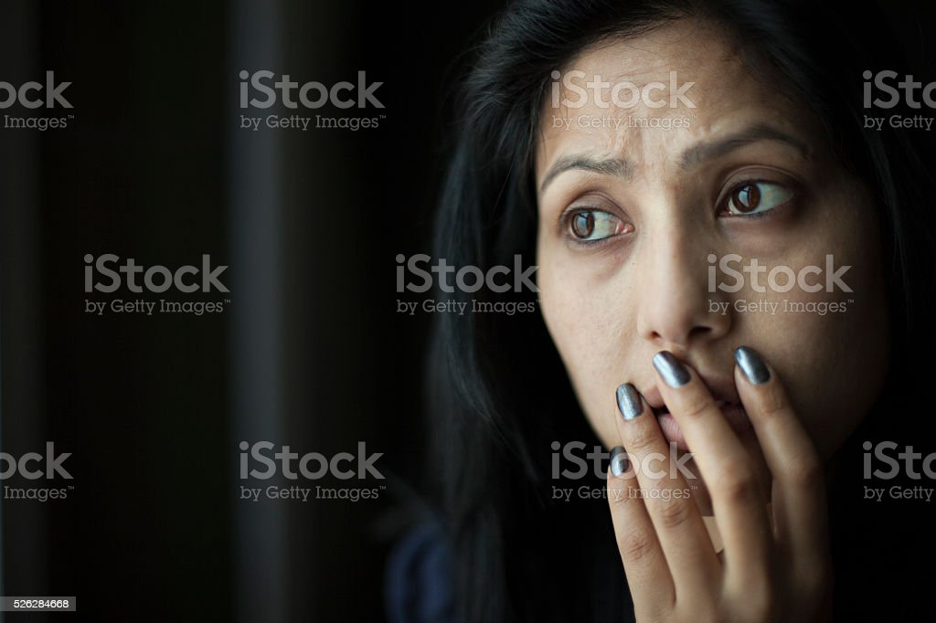 Worried Asian young woman putting her hand on mouth. stock photo