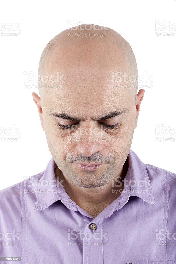 Worried bald  man looking down. stock photo