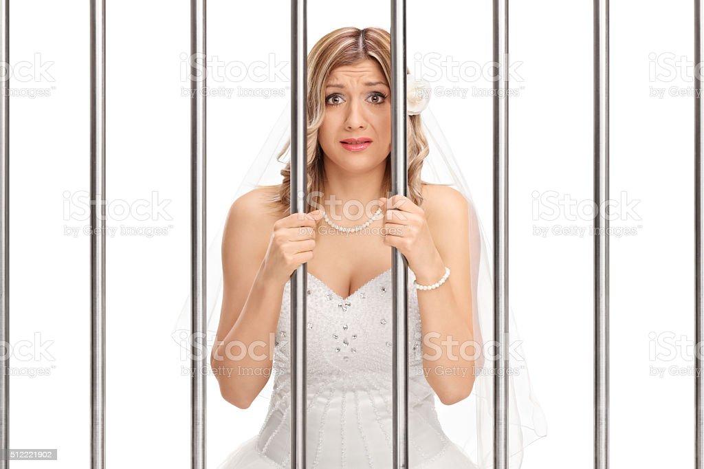 Worried bride standing behind bars in jail stock photo