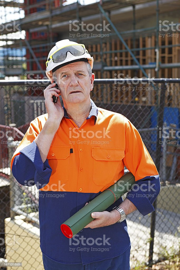 Worried builder on phone royalty-free stock photo