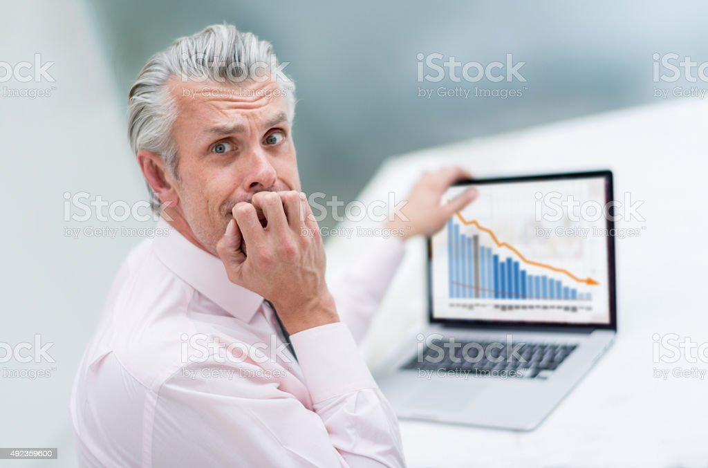 Worried business man looking at a decreasing graph stock photo