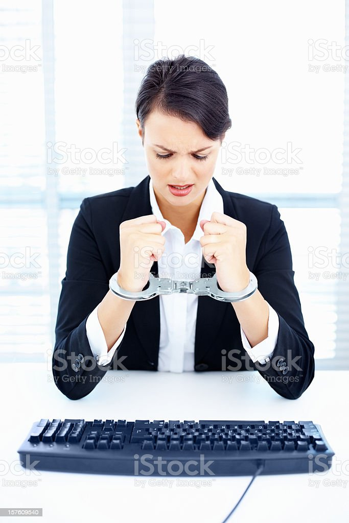 Worried business woman tied up in handcuffs at desk royalty-free stock photo