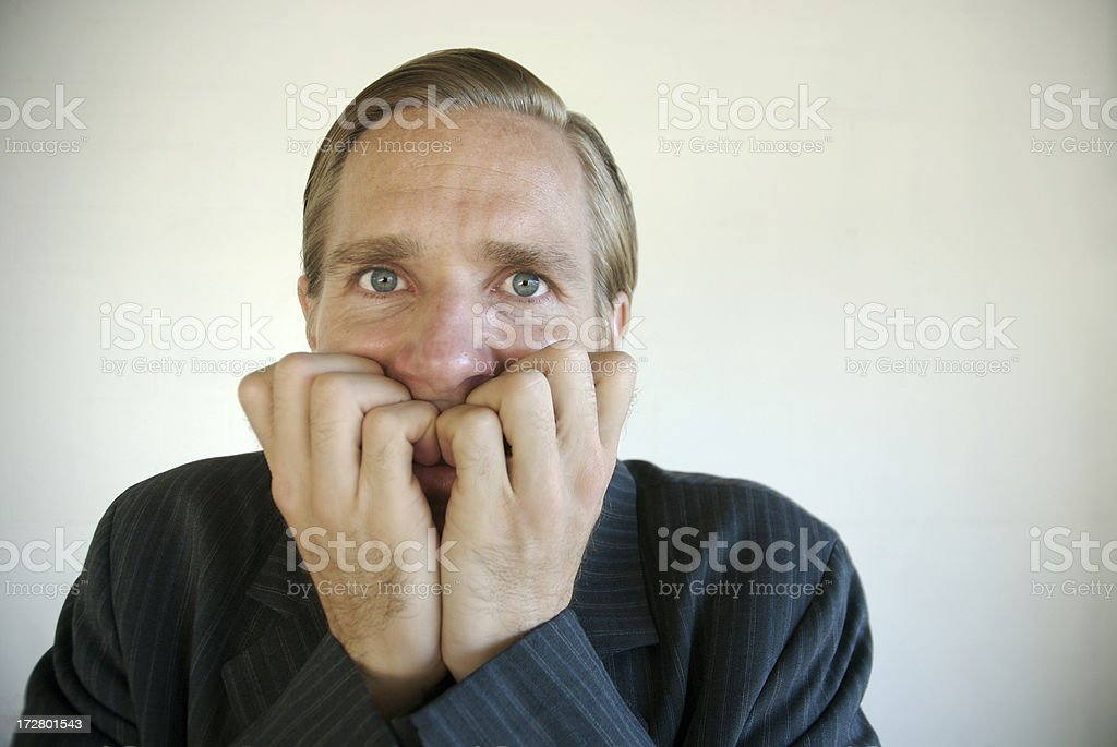 Worried Businessman Biting Nails Looking at Camera stock photo