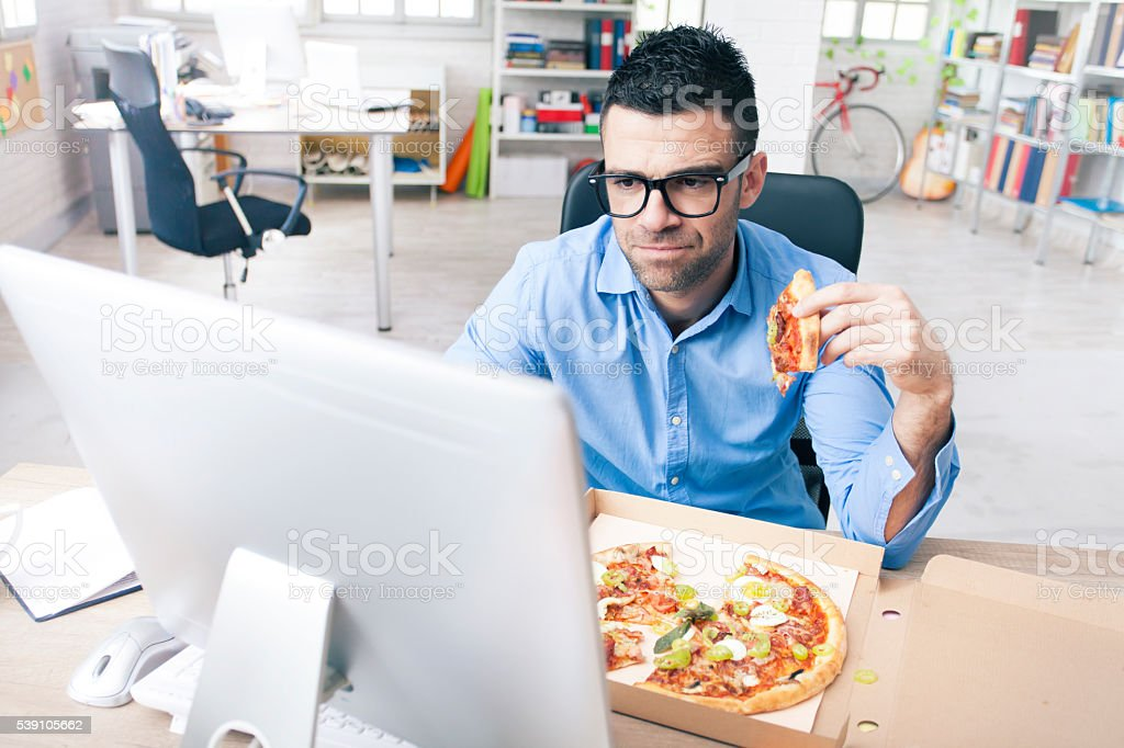 Worried businessman eating pizza at the office stock photo