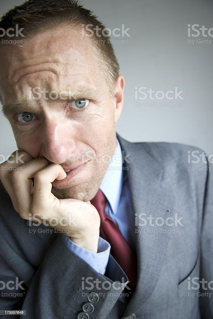 Worried Businessman Looks Stressed Biting Fingers royalty-free stock photo