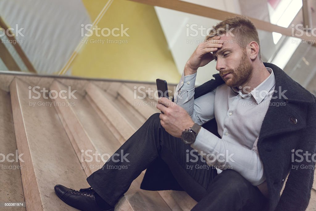 Worried businessman reading a text message on cell phone. stock photo