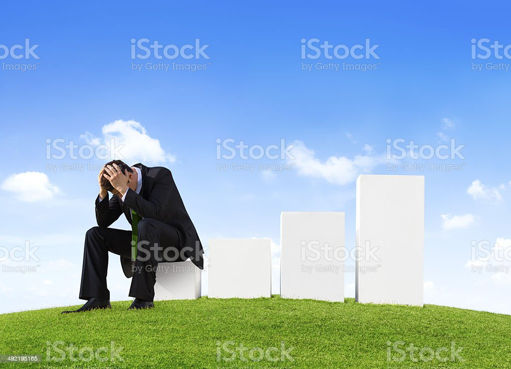 Worried Businessman Sitting on a Bar Graph stock photo