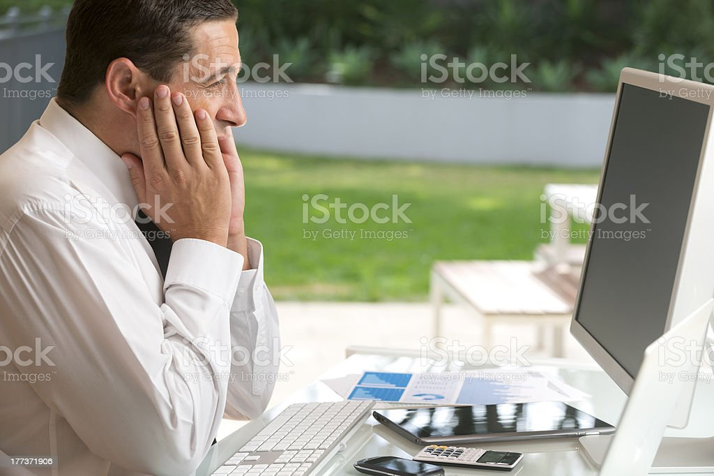 Worried businessman using computer royalty-free stock photo