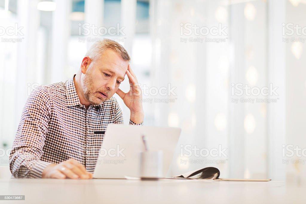 Worried businessman using laptop. stock photo
