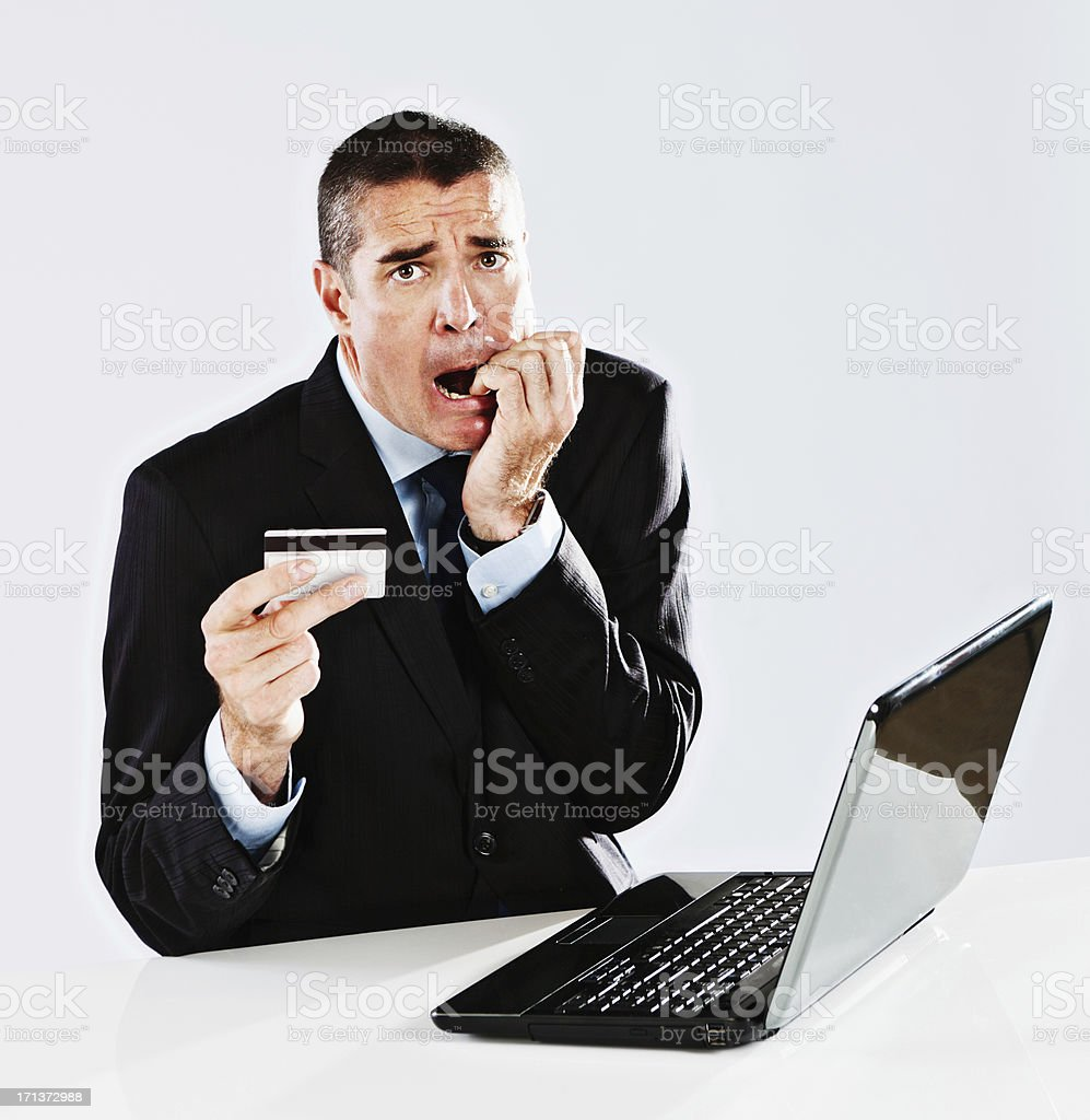 Worried businessman with laptop and credit card: overdone the e-commerce! royalty-free stock photo