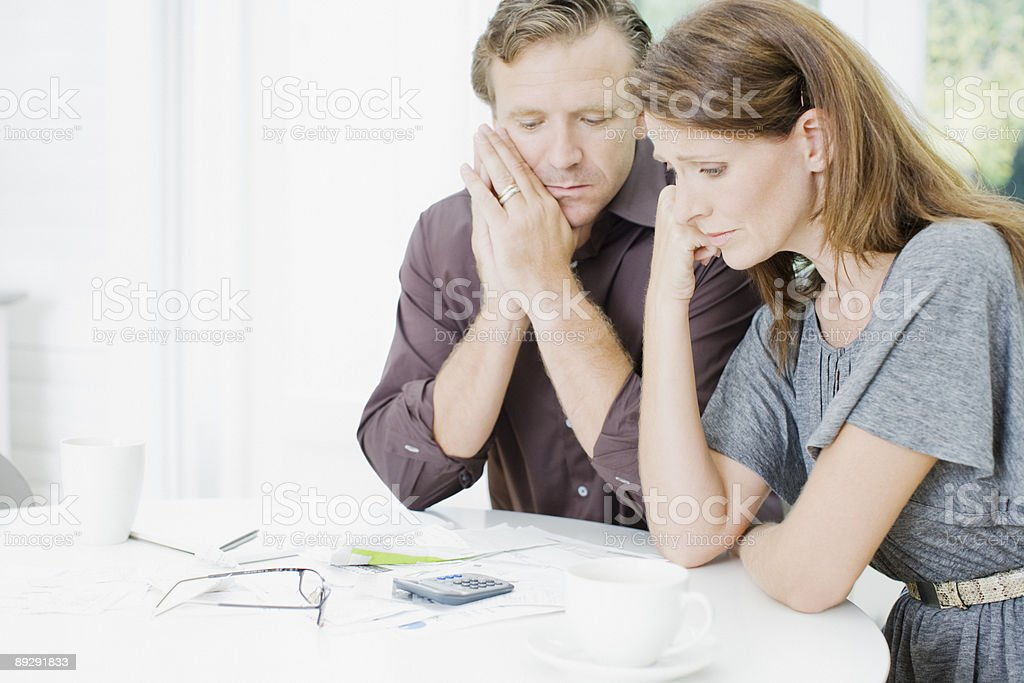 Worried couple at table paying bills royalty-free stock photo