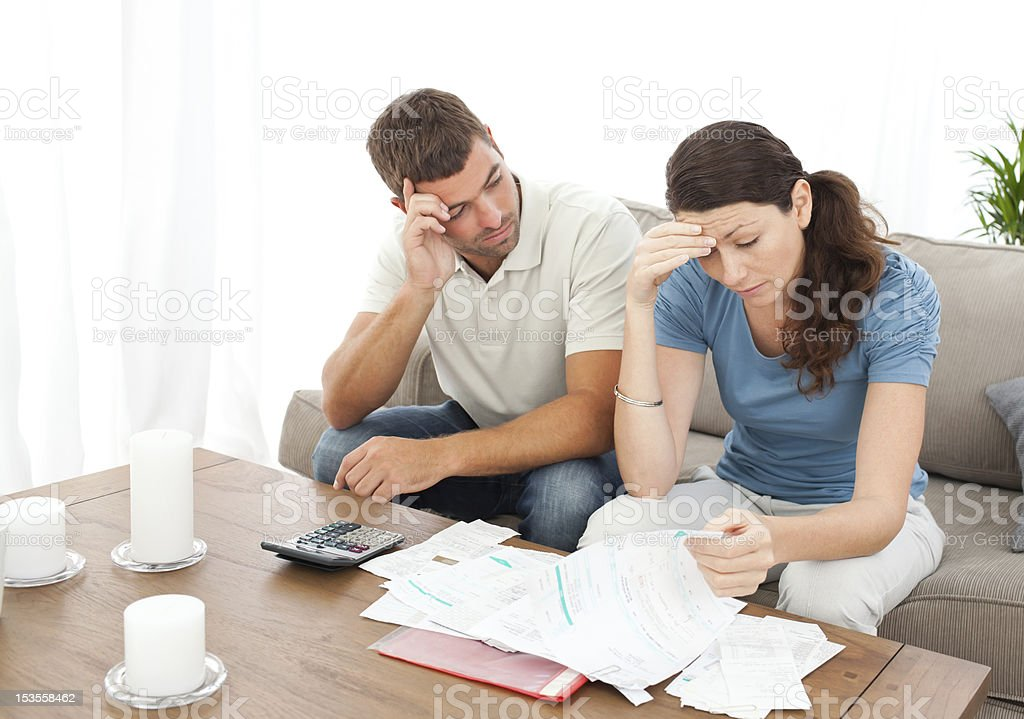 Worried couple doing their accounts in the living room stock photo
