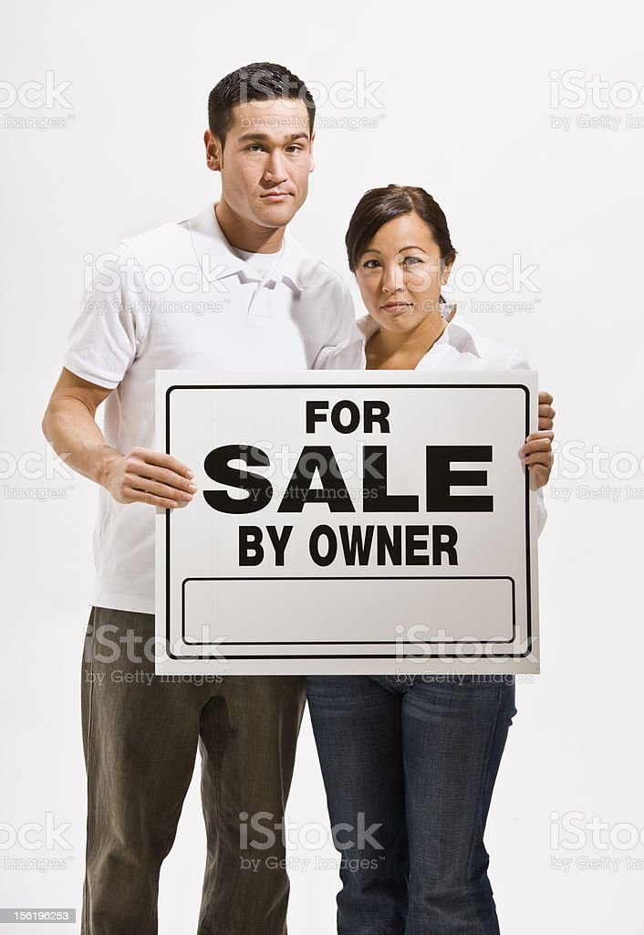 Worried Couple Holding For Sale Sign royalty-free stock photo
