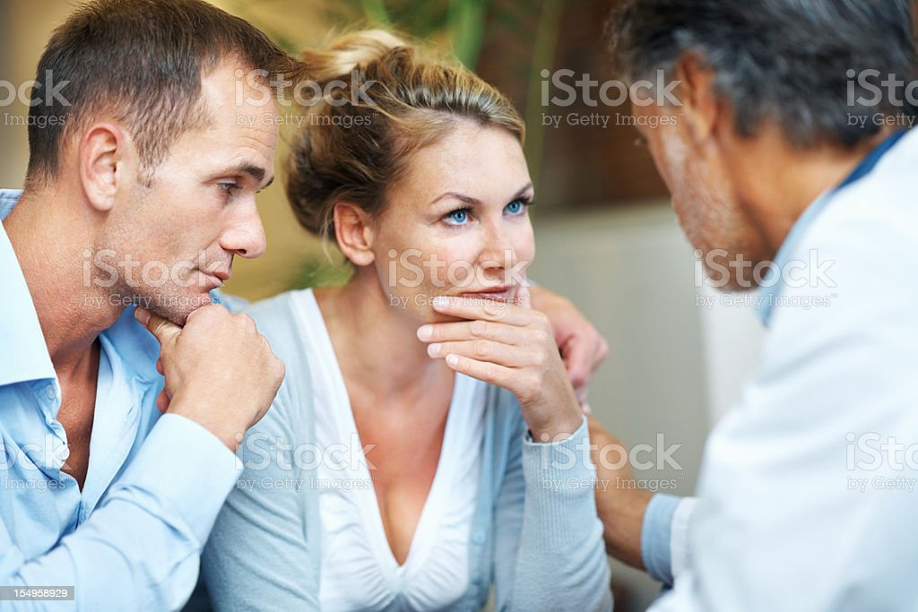 Worried couple in conversation with a doctor royalty-free stock photo