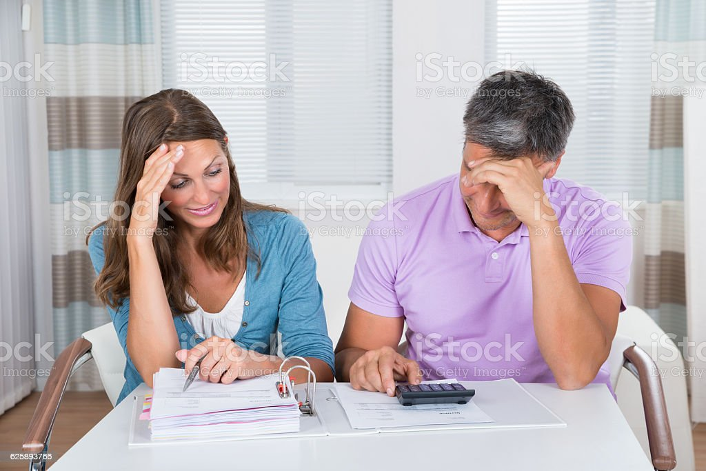 Worried Couple Looking At Unpaid Bills stock photo