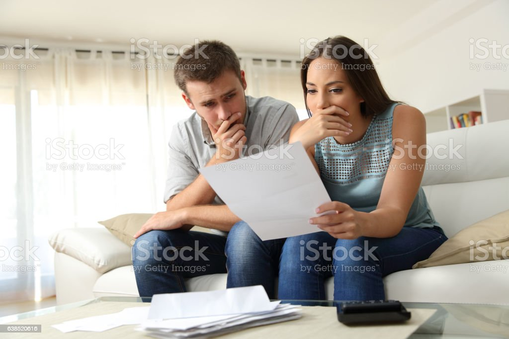 Worried couple reading a letter at home stock photo