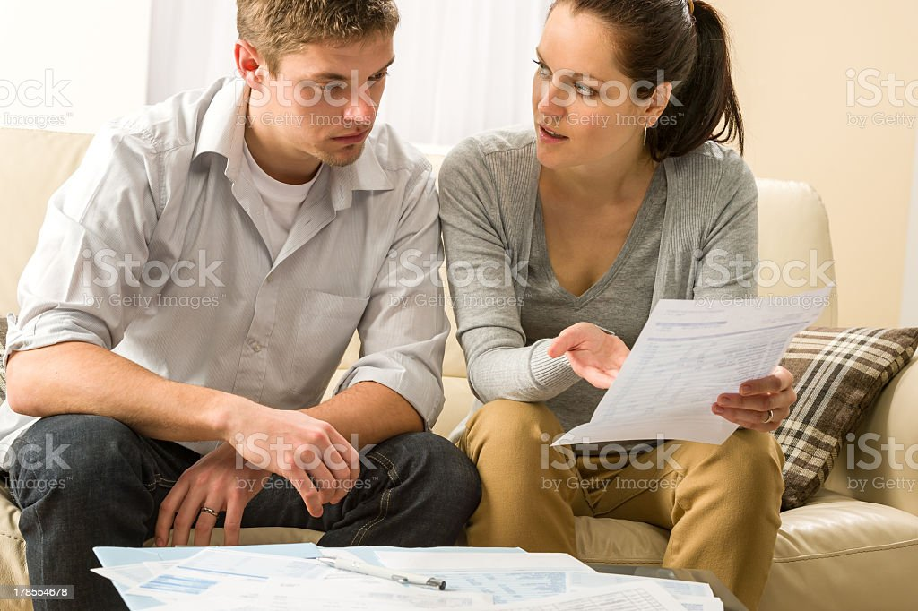 Worried couple talking about their expenses stock photo