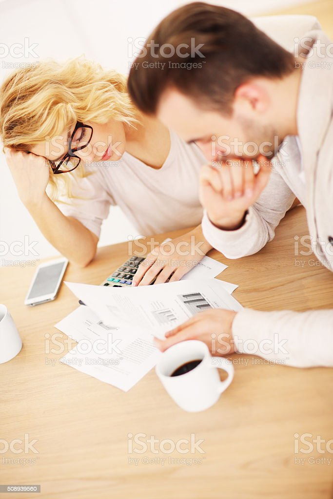 Worried couple with documents at home stock photo