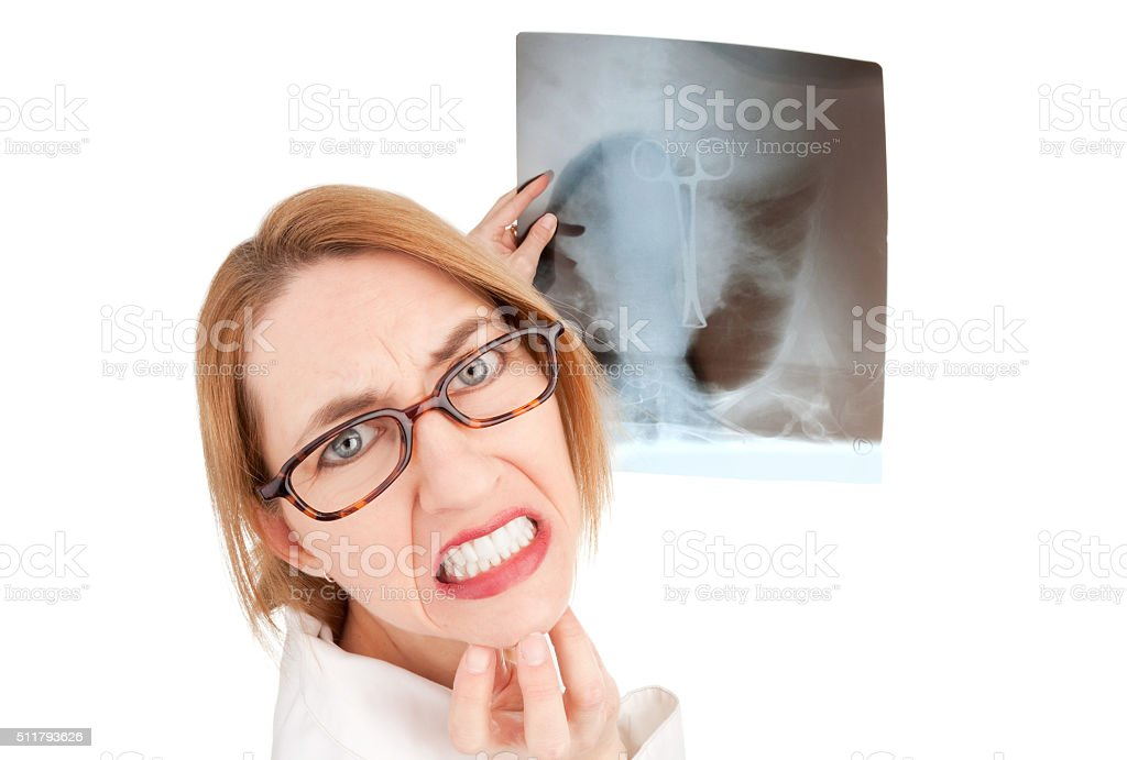 Worried Doctor Holding X-Ray Of Medical Mistake stock photo