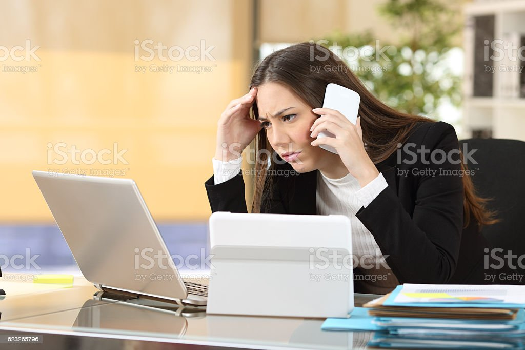 Worried executive with multiple devices stock photo