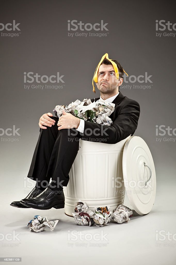 worried failure business man trash can covered by garbage banana stock photo