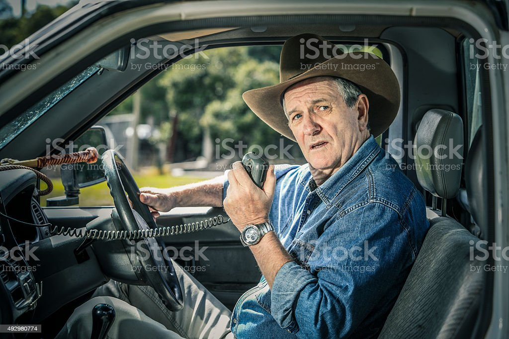 Worried farmer in vehicle looking and listening to message stock photo