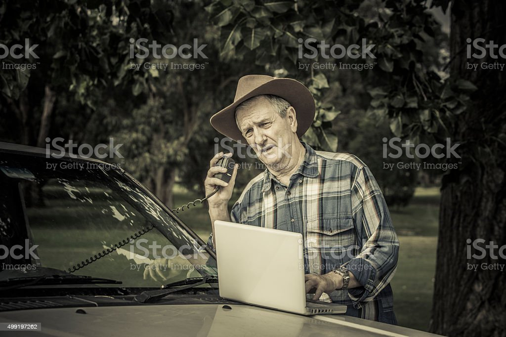 Worried farmer with vehicle talking on radio plus laptop computer stock photo