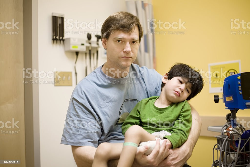Worried father holding his sick disabled son in hospital royalty-free stock photo