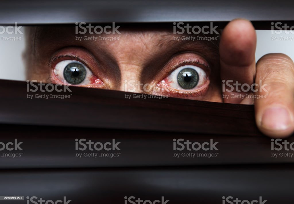 Worried, fearful, mature man peeps through blind, nervously stock photo