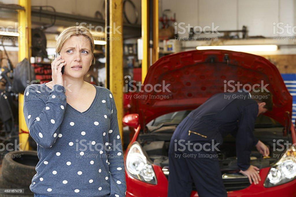 Worried Female Customer On Phone In Garage royalty-free stock photo