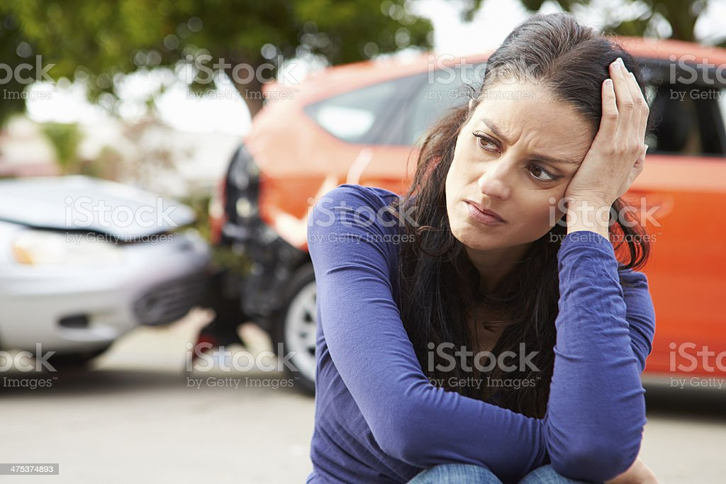 Worried Female Driver Sitting By Car After Traffic Accident stock photo