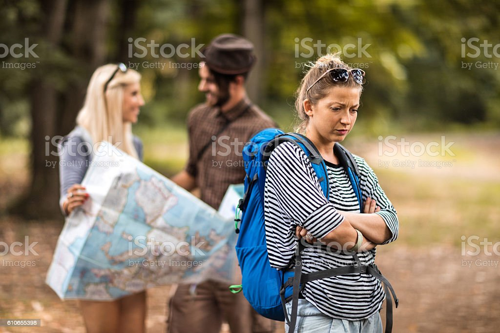 Worried female hiker standing in nature with arms crossed. stock photo