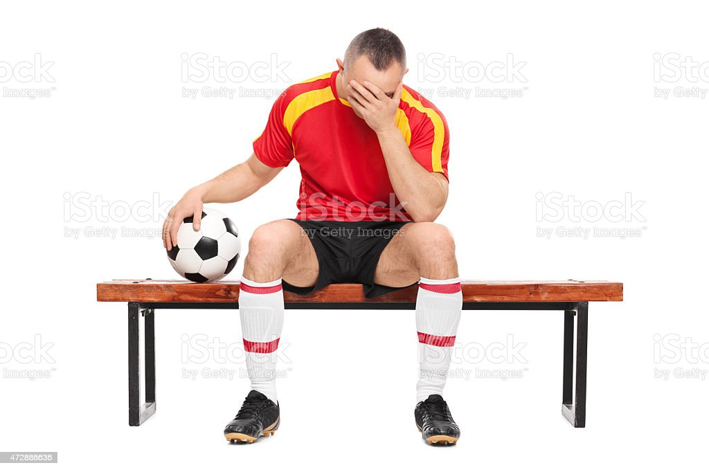Worried football player sitting on a bench stock photo