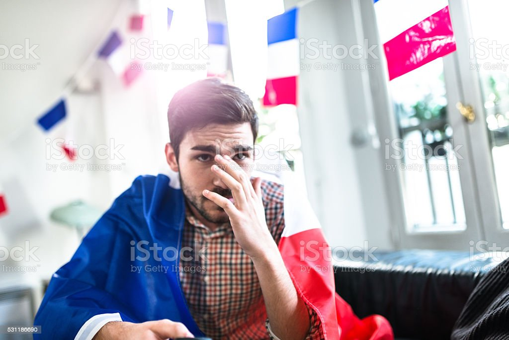 worried France man supporters at home watching the tv stock photo