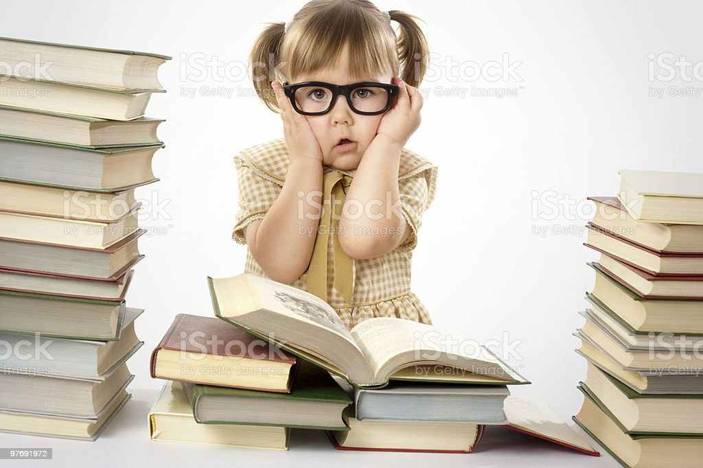 Worried little girl wearing glasses, surrounded by books royalty-free stock photo