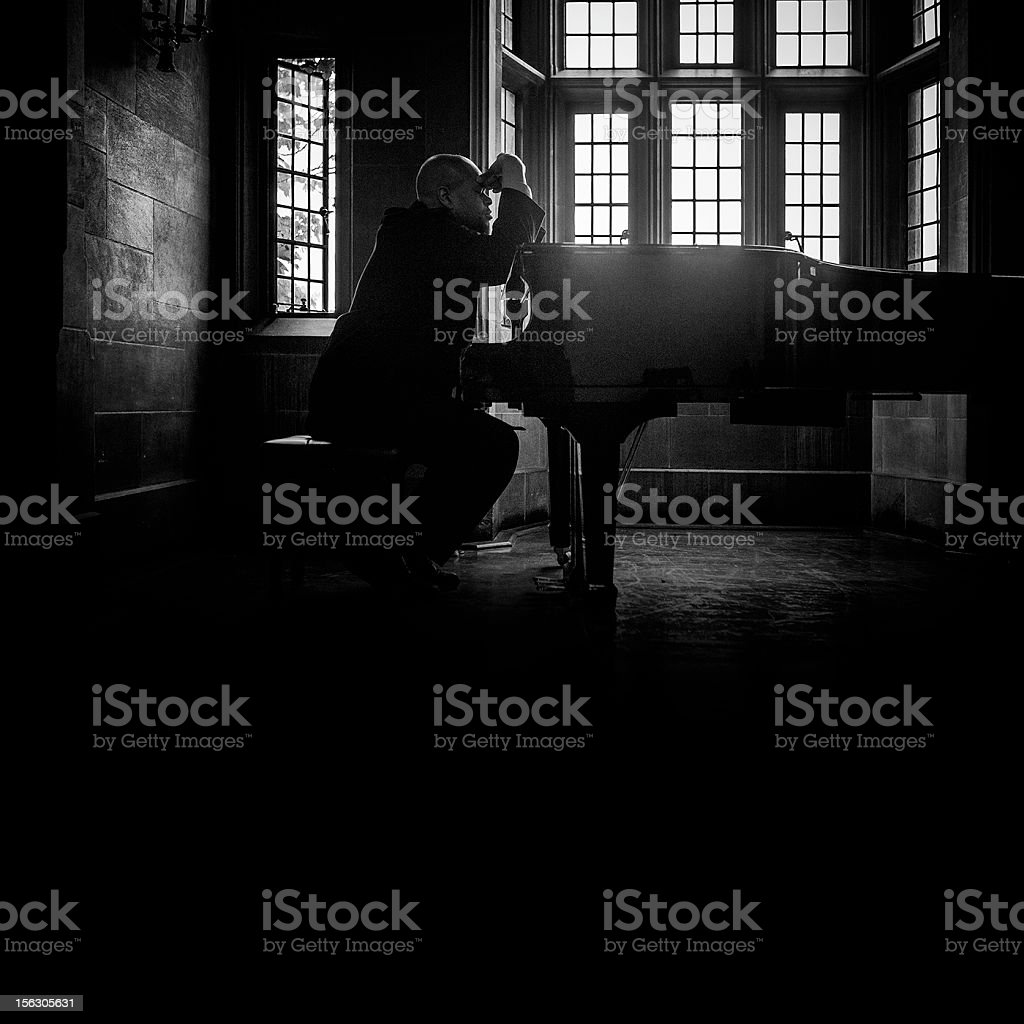 worried man by the piano stock photo