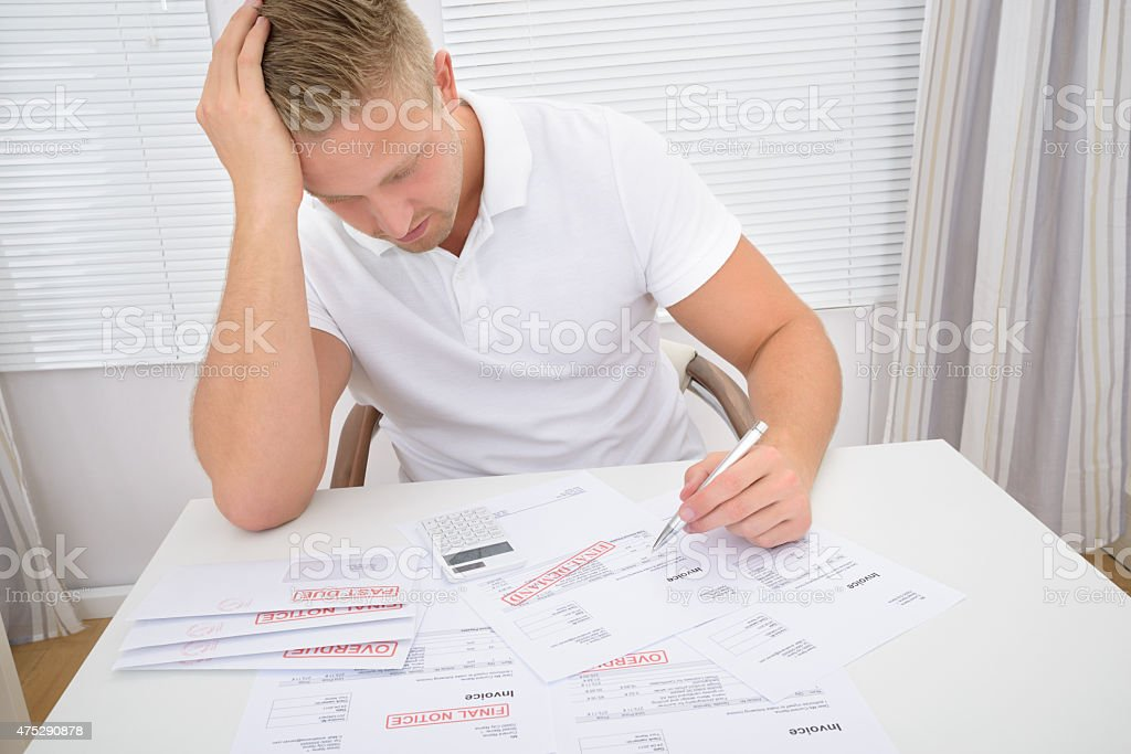 Worried Man Calculating Bills stock photo