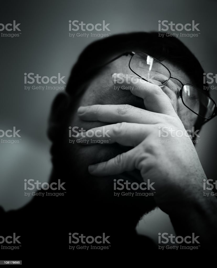 Worried Man Holding Face in Hands, Low Key royalty-free stock photo