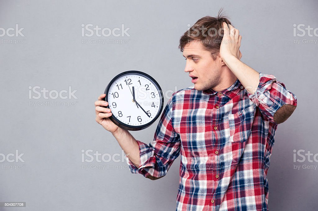 Worried man in checkered shirt holding and looking at clock stock photo