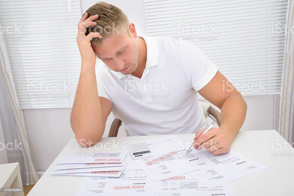 Worried Man Looking At Bills stock photo