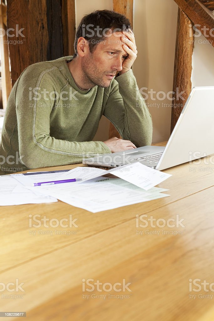 Worried Man Looking at Laptop with Papers Beside Him royalty-free stock photo