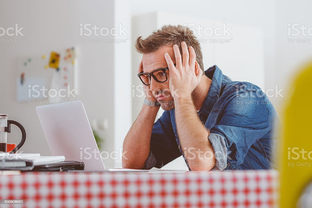 Worried man looking at the laptop screen stock photo