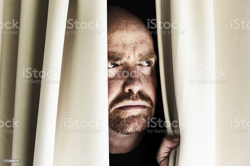 Worried man looks through closed curtains, frowning stock photo