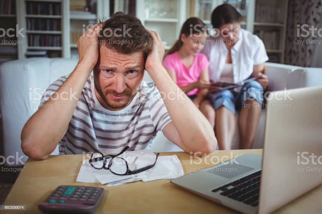 Worried man sitting at table with bills and laptop stock photo