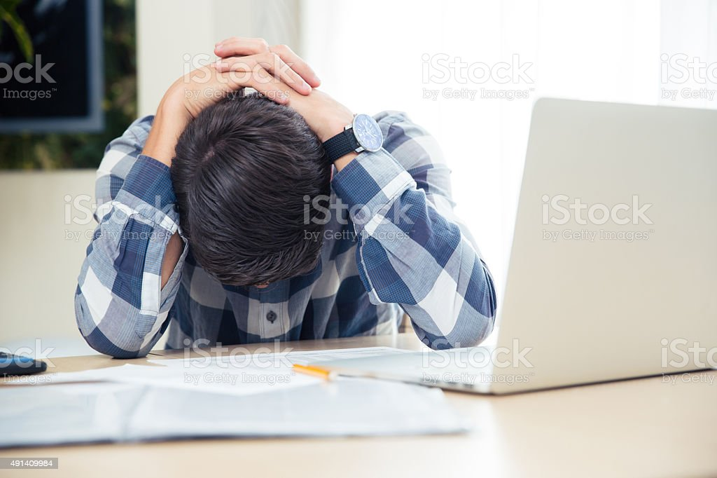 Worried man sitting at the table stock photo