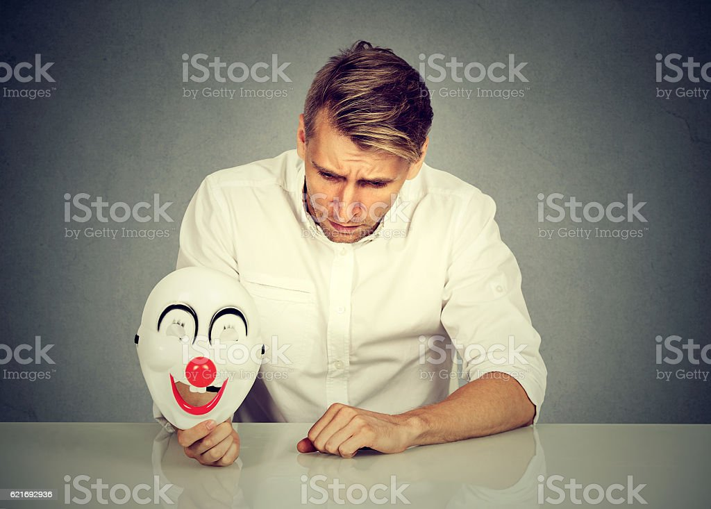 worried man with sad expression holding clown mask stock photo