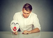 worried man with sad expression holding clown mask
