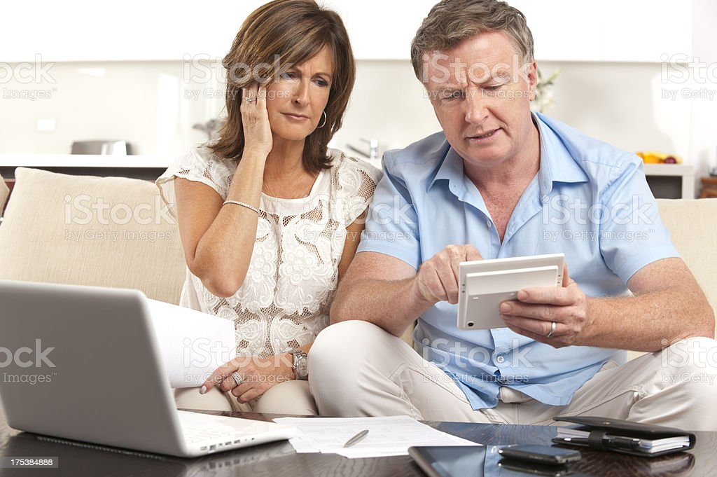 Worried Mature couple doing paperwork with a calculator stock photo
