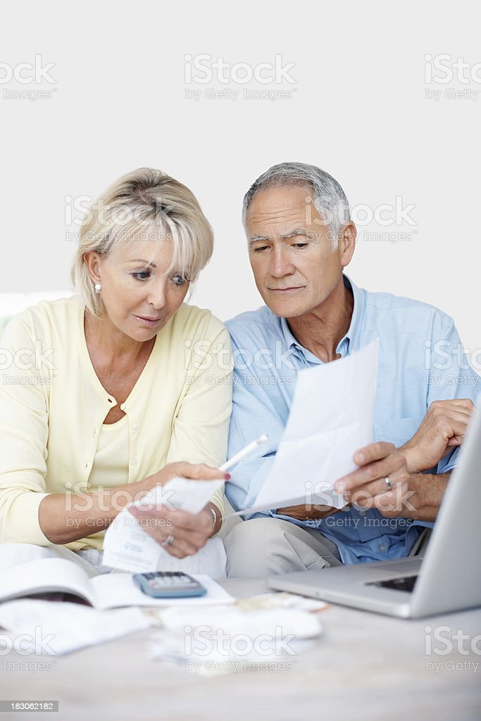 Worried mature couple reading their monthly expenses at home royalty-free stock photo